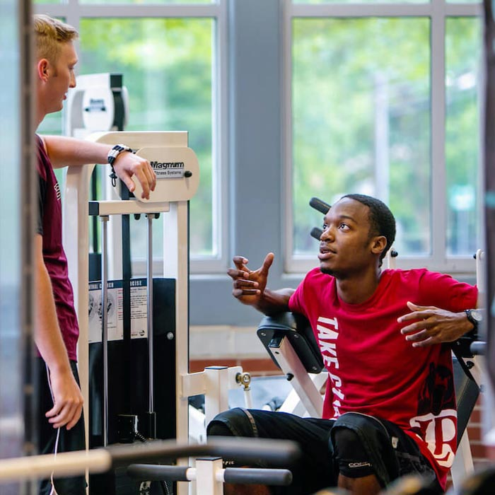 Two students talking in fitness center