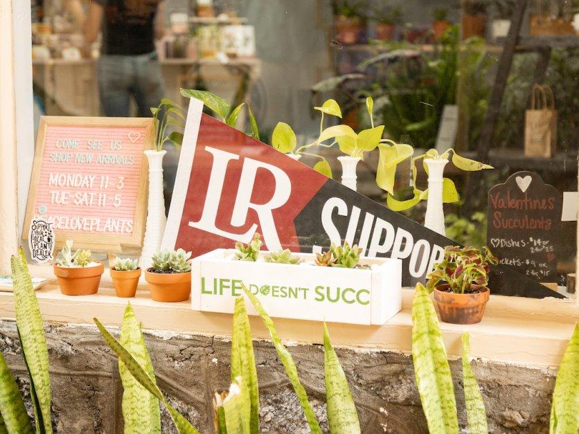 A shop window features an LR supporter flag.