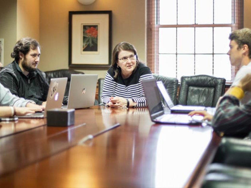 Student investors talk with professor seated around a conference table