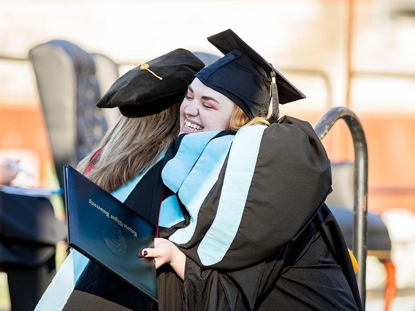 Graduating students hug