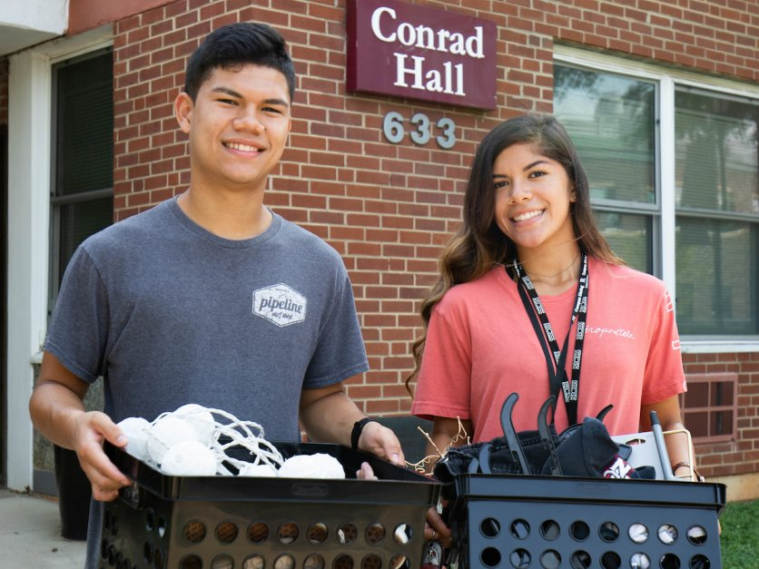 Two students cart boxes into Conrad Hall as part of move in.