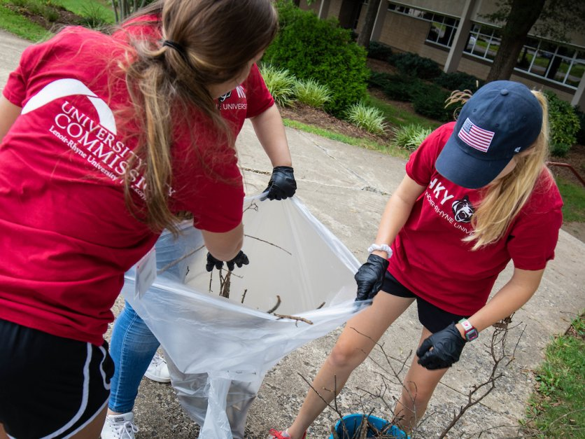 Three student volunteers clean up yard debris as part of a community service project.