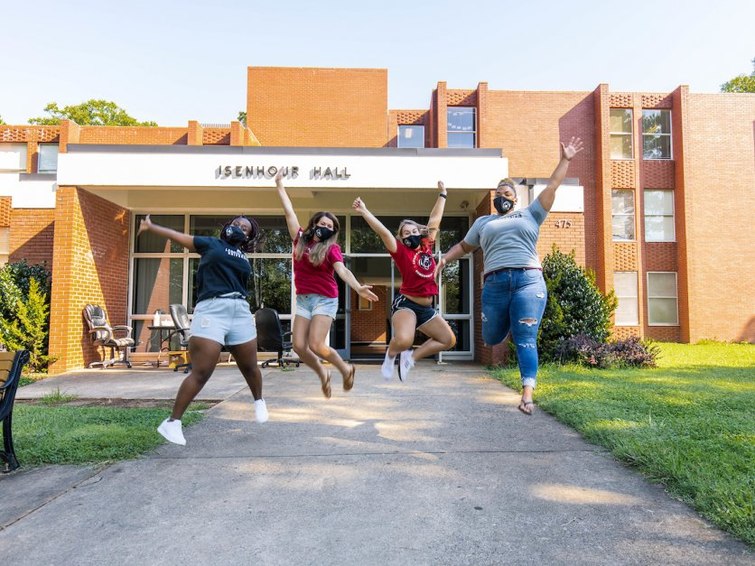 Four students jump into the air in front of Isenhour Hall.