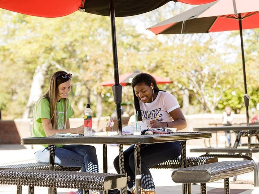 Students laughing and studying under an umbrella in Shaw Plaza