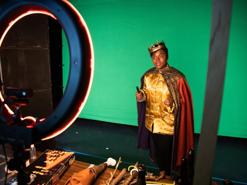 A student dressed in costume performs lines in front of a green screen