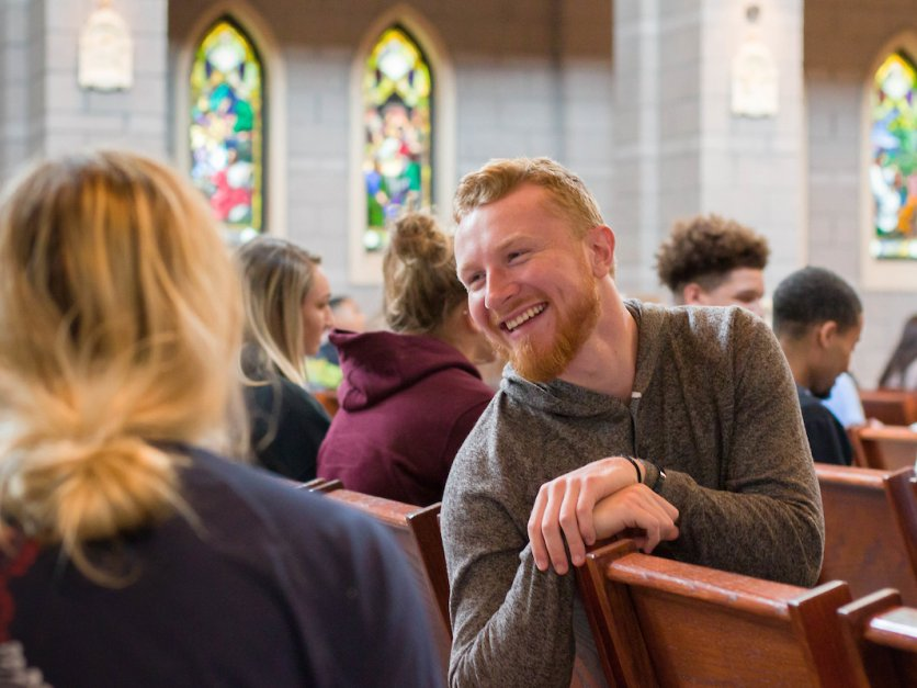 A student looks back at other while talking and smiling in chapel.