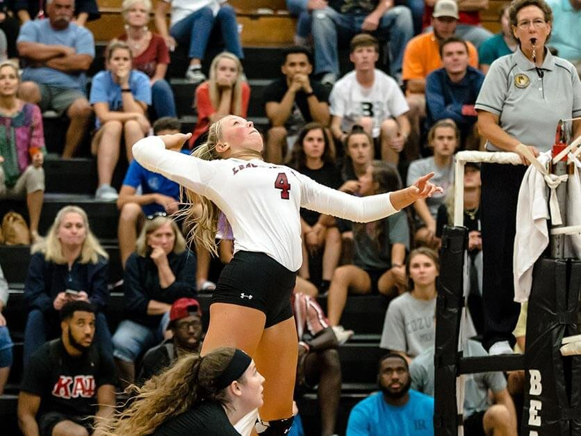 A volleyball player spikes the ball