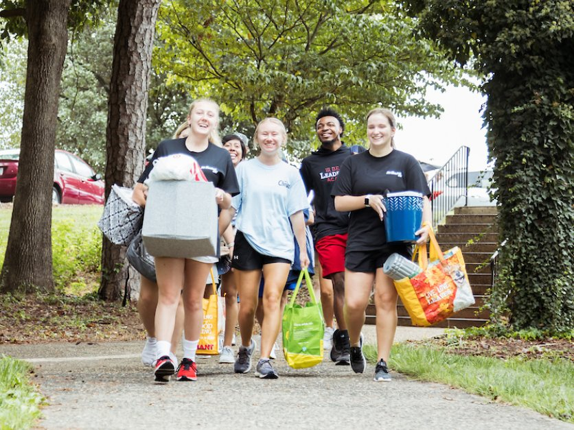 Students carry bags and boxes to a dorm during move-in.