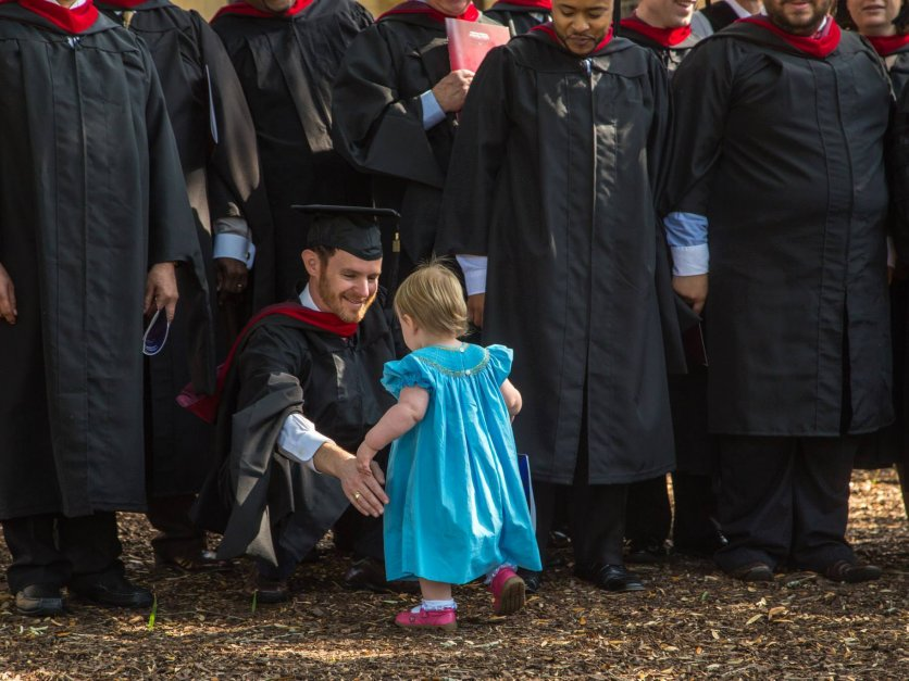 A graduate kneels down to hug his young daughter.