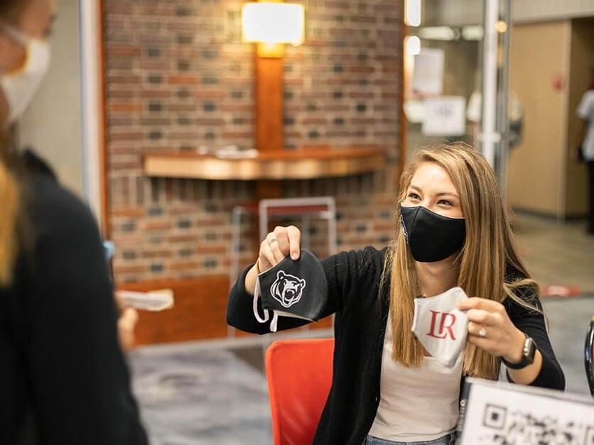 A student worker hands out LR masks