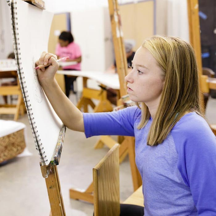 Student working on canvas in art class