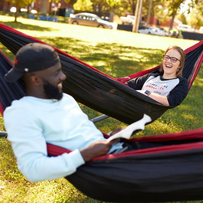 Two students laughing while studying in hammocks on lawn